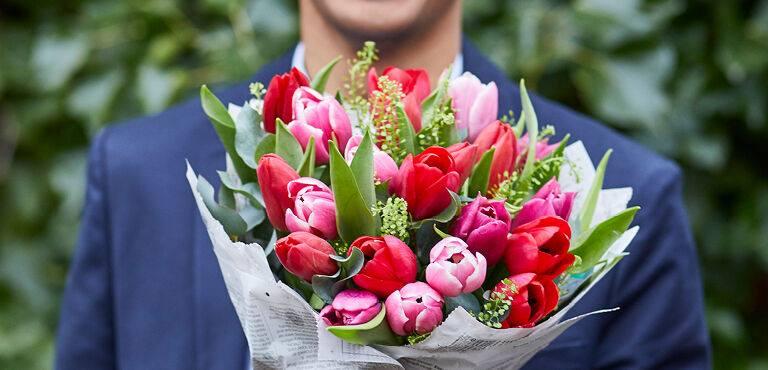 Man met een boeket van rode en roze tulpen
