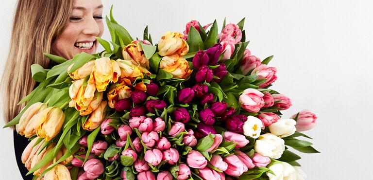 Femme tenant un gros bouquet de tulipes multicolores