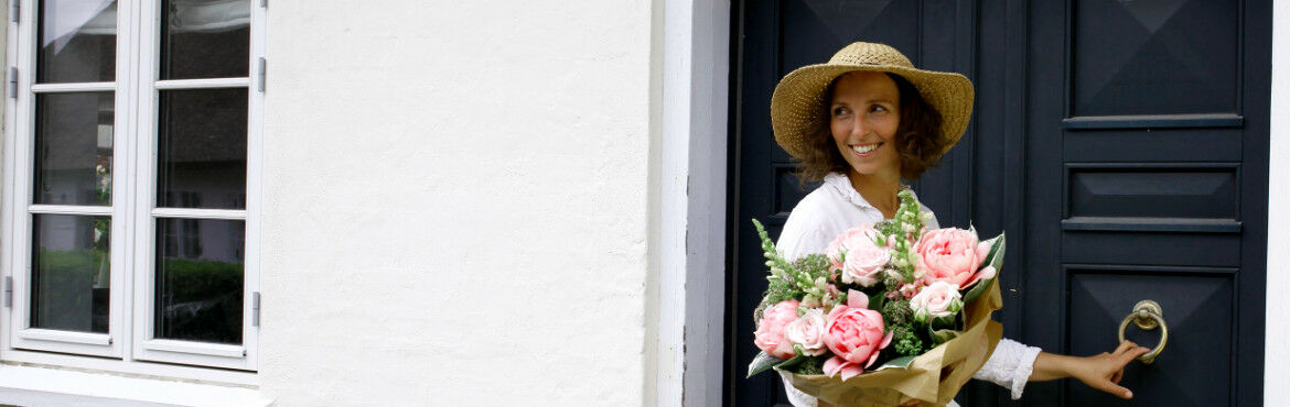 A woman standing in front of a door holding a bouquet of peonies in her hands
